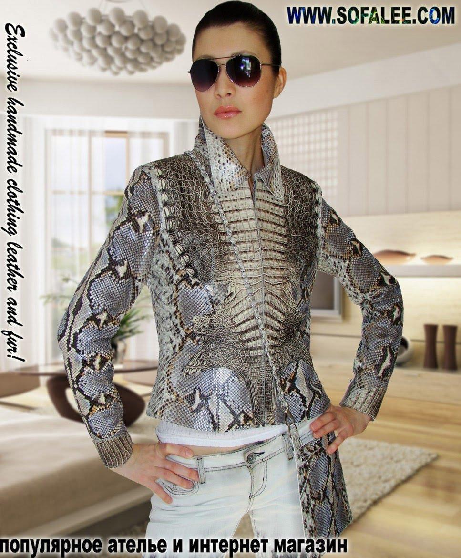Красивая девушка в шикарной куртке из крокодила и питона от модельера Sofalee, стоит на фоне современной квартиры